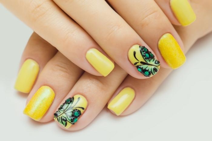 idée manucure pour ongles mi-longs de couleur jaune avec dessin sur l'annulaire à design papillon vert avec strass noirs
